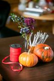 How to make a Thanksgiving centerpiece with big pumpkin and bouquet of flowers. stock image