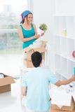 How to pack it?. Vertical image of a couple packing things together in a room Royalty Free Stock Photo