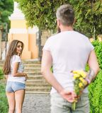 How to pick up girl. Girl looks at man with bouquet with interest. Start dating. Golden rules for asking women out. How to pick up girl. Girl looks at men with royalty free stock photography