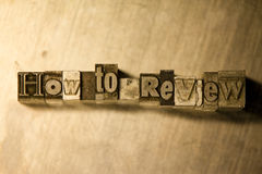 How to review - Metal letterpress lettering sign. Lead metal  typography text on wooden background Stock Images