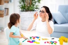 How to save healthy eyesight. Mom and daughter make glasses from plasticine.  stock image