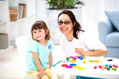 How to save healthy eyesight. Mom and daughter make glasses from plasticine.  stock images