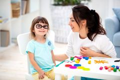 How to save healthy eyesight. Mom and daughter make glasses from plasticine.  royalty free stock photo