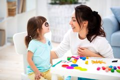 How to save healthy eyesight. Mom and daughter make glasses from plasticine.  stock photography