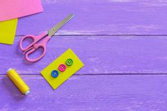 Colourful buttons on yellow felt piece. Scissors, thread, needle, felt pieces on a wooden background with copy space for text Stock Images