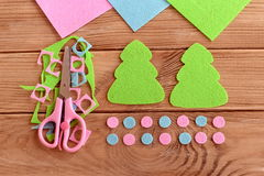 How to sew Christmas decoration. Step. Felt Christmas tree patterns, felt scraps, scissors on wooden background. Homemade crafts. Winter needlework project for royalty free stock photo