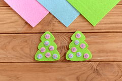 How to sew Christmas decoration. Step. Green felt Christmas tree decorated with pink and blue circles on a wooden background. Christmas tree embroidery. Kids royalty free stock photography