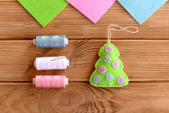 How to sew Christmas decoration. Step. Green felt Christmas tree embellishment, thread, needle on a wooden table. Hanging ornament Christmas tree. Simple and Royalty Free Stock Image