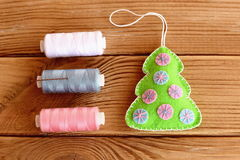 How to sew Christmas ornament. Step. Felt Christmas tree ornament, thread set, needle on a wooden background Stock Images