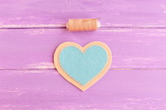 How to sew a felt heart decor. Step. Join blue and beige felt pieces using beige thread. Sewing kit on wooden background Royalty Free Stock Photography