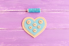 How to sew a felt heart decor. Step. Join the felt edges of felt heart with blue thread. Blue thread, needle on wooden background Stock Photos