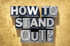 How to stand out. Question made from metallic letterpress type on grunge cardboard background Royalty Free Stock Photo