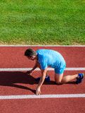 How to start running. Running tips for beginners. Man athlete stand low start position at stadium path. Beginning of new stock photo