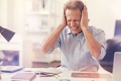 Depressed mature man suffering from a headache. How to stop it. Depressed mature man sitting in the office and feeling ill while suffering from a terrible Stock Image
