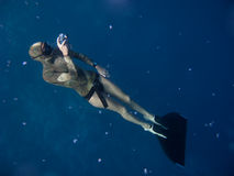 How to take freediving pictures. Freediver with monofin takes photo while standing under the surface royalty free stock photo