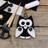 Stuffed felt owl toy, black and white felt sheets, scissors, threads, buttons on an vintage wooden background. How to teach a child to sew by hand at home Stock Images