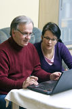 How to use laptop. A woman (daughter) teaching a senior man (father) how to use a laptop Royalty Free Stock Photography