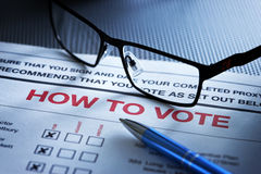 Voting Vote Form Shareholder Meeting. A shareholder how to vote form with pen and reading glasses still life stock photos