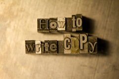 How to write copy - Metal letterpress lettering sign. Lead 'How to write copy' typography text on wooden background Stock Photo