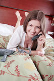 How are you?. Young relaxed and smiling woman talking by phone in bed Royalty Free Stock Photography