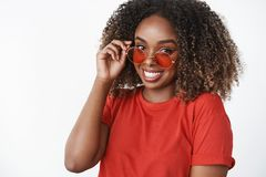How You Doing Sunny. Portrait Of Cute African-american Modern Woman In Red T-shirt And Trendy Sunglasses Touching Rim Stock Photography