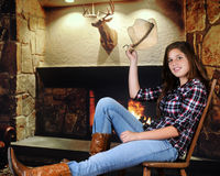 Howdy by the Fireplace. A pretty young teenage cowgirl tipping her hat in greeting as she rests near a fireplace royalty free stock image