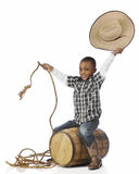 Howdy! I`m a Cowboy. A happy young boy smiling at the viewer as he `ridies` an old barrel as he plays cowboy.  On a white background Royalty Free Stock Image
