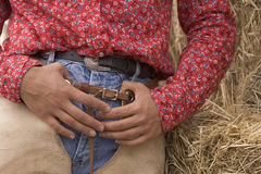 Howdy Partner. Close up view of cowgirl hands and torso- thumbs hooked in chaps at her waist Stock Photography