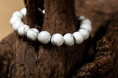 The howlite stone bracelet. On the stump wood royalty free stock photo