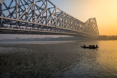 Howrah bridge Kolkata at dawn with wooden boat on river Hooghly. Royalty Free Stock Photos