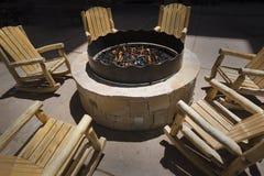 Hoyo al aire libre grande del fuego rodeado por las mecedoras de madera Fotografía de archivo