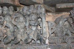 Hoysaleswara寺庙使用望远镜的墙壁雕刻一个人 库存照片