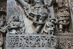 Hoysaleswara寺庙墙壁雕刻了与鹰报有人的特点的鸟雕塑在祈祷的姿势的 库存图片