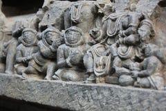 Hoysaleswara雕刻看起来有他们的小配件的古老外籍人宇航员的寺庙墙壁 免版税库存图片