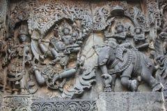 Hoysaleswara-Tempel außerhalb der Wand schnitzte mit der Skulptur von Lord Indira Lord krishna für den Diebstahl von parijatha Bl Lizenzfreie Stockfotografie