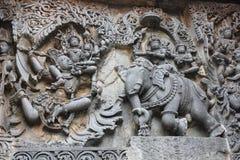 Hoysaleswara-Tempel außerhalb der Wand schnitzte mit der Skulptur von Lord Indra Lord krishna für den Diebstahl von parijatha Blu Stockfotografie
