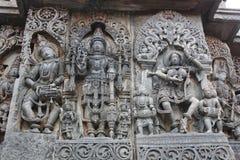 Hoysaleswara-Tempel-Wand schnitzte mit Skulptur von Lord mahavishnu zwischen den Skulpturen des Musikers und des Tänzers Stockfotografie