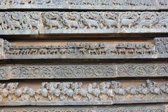 Hoysaleswara tempelvägg som snider med skulpturer av makaraen, hästar och dragkampen Royaltyfri Fotografi