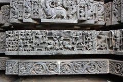 Hoysaleswara tempelvägg som snider visa den forntida krigplatsen Arkivfoto