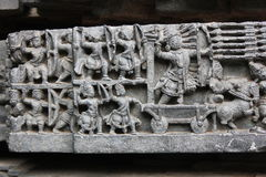 Hoysaleswara tempelvägg som snider visa den forntida krigplatsen Fotografering för Bildbyråer