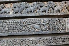 Hoysaleswara tempelvägg som snider visa den forntida krigplatsen Royaltyfri Fotografi