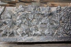 Hoysaleswara tempelvägg som snider visa forntida stridplats Arkivfoton