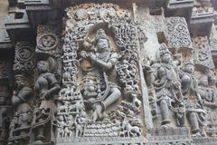 Hoysaleswara Temple outer wall carved with sculpture of Lord Krishna playing flute Stock Image