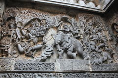 Hoysaleswara Temple outside wall carved with sculpture of Lord Indira chasing Lord krishna for stealing parijatha flower Royalty Free Stock Photo
