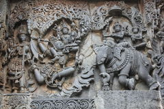 Hoysaleswara Temple outside wall carved with sculpture of Lord Indira chasing Lord krishna for stealing parijatha flower Royalty Free Stock Photography