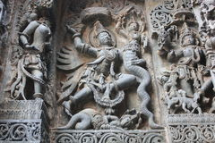 Hoysaleswara Temple wall carved with sculpture of Garuda humanoid bird fighting with Nagas Serpents Royalty Free Stock Photos