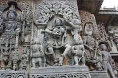 Hoysaleswara Temple wall carving of beautiful female dancer in between the musicians. This is a wall carving of beautiful female dancer in between the musicians stock image