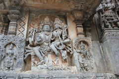 Hoysaleswara Temple Wall Carving of Lord Shiva with his wife Parvati and holding japa mala or rosary beads Stock Image
