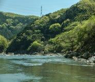 Hozugawa River by the rocky green hills. Hozugawa River along the rocky green hills with power lines. Arashiyama, Kyoto. Japan Stock Image