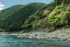 Hozugawa River by the rocky green hills. Hozugawa River along the rocky green hills with train bridge. Arashiyama, Kyoto. Japan Stock Images
